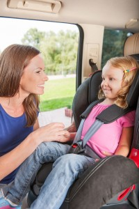 Mother helps her daughter to fasten belt on car seat